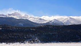 Снег и облака дуют над пиками скалистых гор Стоковое Изображение RF