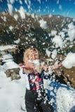 Снег молодой белокурой кавказской женщины бросая стоковое изображение rf