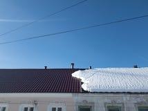 Снег на половине крыши дома В половине Плавя снег на крыше стоковое фото