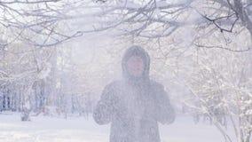 Снег падает от ветви Человек покрывает его голову с клобуком движение медленное сток-видео