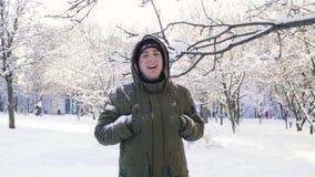 Снег падает от ветви Человек покрывает его голову с клобуком движение медленное видеоматериал