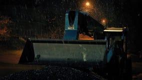 Снег падая на машину землекопа на ноче акции видеоматериалы
