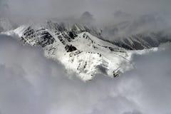 Снег покрыл горную цепь среди белых облаков кумулюса, зиму в Гималаях Стоковое фото RF