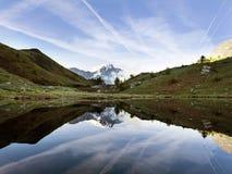 Снег покрыл гору около col de vars в французской Провансали отраженной в воде небольшого озера стоковое изображение