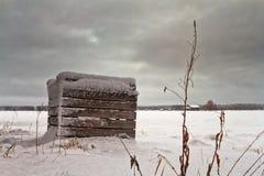 Снег покрыл деревянную клеть на полях Стоковые Фото
