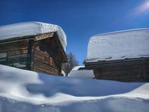 Снег покрыл деревянные коттеджи в швейцарских горных вершинах стоковое изображение rf