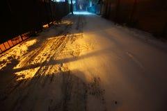 Снег покрыл пригородную дорогу освещенную уличными светами на nighttime Стоковое Фото