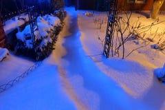 Снег покрыл путь освещенный уличными светами на nighttime Стоковая Фотография RF