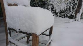 Снег покрыл стул снаружи в саде Стоковое Изображение