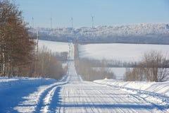 Снег покрыл сельские дорогу и ветротурбины Стоковые Фото