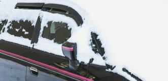Снег покрыл черный автомобиль Стоковые Фото
