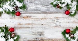 Снег рождества покрыл вечнозеленые ветви и красное decoratio шарика стоковая фотография