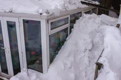 Снег сложил вверх высоко на стороне консерватории Стоковые Изображения RF
