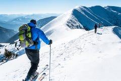 Снег skialpinists группы покрыл горы стоковое изображение rf