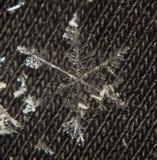 Снежинка близкая вверх на сером материале Стоковое фото RF