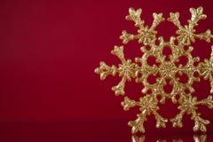 Снежинка рождества золотая на темноте - красной предпосылке с космосом для текста Стоковое фото RF