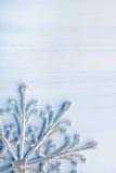 Снежинка рождества серебряная на свете - голубой деревянной предпосылке с космосом для текста стоковая фотография