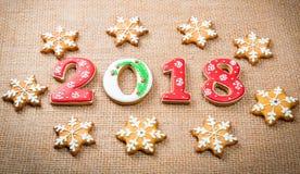 Снежинки и 2018 печений пряника рождества на предпосылке мешковины Стоковые Изображения