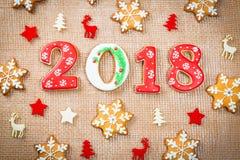 Снежинки и 2018 печений пряника рождества на предпосылке мешковины Стоковое Фото