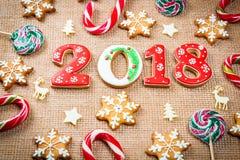 Снежинки и 2018 печений пряника рождества на предпосылке мешковины Стоковые Изображения RF