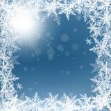 Снежинки и солнце рождества на голубой предпосылке Стоковая Фотография