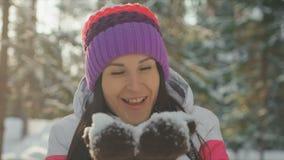 Снежинки счастливой милой молодой женщины дуя от ее рук в зимнем дне сток-видео