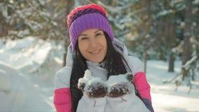 Снежинки счастливой милой молодой женщины дуя от ее рук в зимнем дне акции видеоматериалы