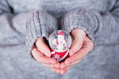 Снежный ком красивого рождества стеклянный в женских руках на предпосылке Стоковое Изображение