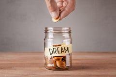 сновидение Стеклянный опарник с монетками и надпись мечтают Человек держит монетку в его руке Стоковая Фотография RF