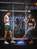 Сногсшибательная девушка разрабатывая с stepper в предпосылке спортзала Тренировка женщины с молодым тренером в фитнес-клубе Стоковые Фотографии RF