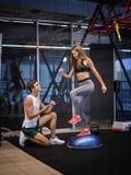Сногсшибательная девушка разрабатывая с stepper в предпосылке спортзала Тренировка женщины с молодым тренером в фитнес-клубе Стоковое Изображение RF
