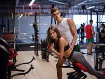 Сногсшибательная женщина делая тренировки на имитаторе на предпосылке спортзала Спорт, фитнес, образ жизни и концепция людей Стоковое Фото
