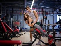 Сногсшибательная женщина делая тренировки на имитаторе на предпосылке спортзала Спорт, фитнес, образ жизни и концепция людей Стоковое Изображение