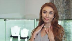 Сногсшибательная красная с волосами женщина пробуя на ожерелье жемчуга на ювелирном магазине стоковое фото