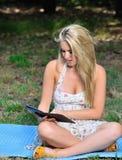 Сногсшибательная молодая белокурая женщина в sundress - чтение Стоковые Фотографии RF