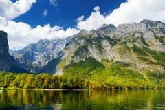 Сногсшибательные глубокие ые-зелен воды Konigssee, известные как ` s Германии самое глубокое и самое чистое озеро, расположенное  Стоковое Изображение RF