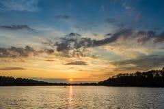 Сногсшибательный заход солнца на озере с одной шлюпкой в лете Стоковая Фотография RF