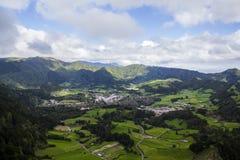 Сногсшибательный ландшафт с полями фермы, зелеными холмами, деревней и лагуной Стоковое Фото