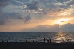 Сногсшибательный силуэт людей на песочном отголоске приставает наслаждаться к берегу заходом солнца Задний взгляд диаграмм людей  Стоковое Изображение RF