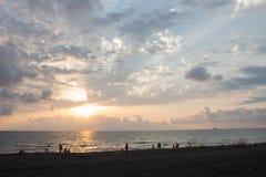 Сногсшибательный силуэт людей на песочном отголоске приставает наслаждаться к берегу заходом солнца Задний взгляд диаграмм людей  Стоковое фото RF