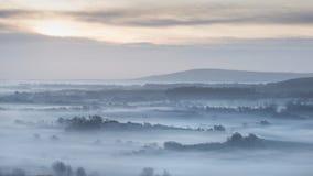 Сногсшибательный туманный английский сельский ландшафт на восходе солнца в зиме с Стоковые Фотографии RF