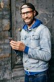 Сногсшибательный человек при голубые глазы, крышка бороды и широкой улыбки нося, рубашка джинсовой ткани и eyeglasses держа smart стоковые изображения rf
