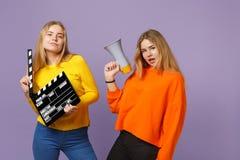 2 сногсшибательных молодых белокурых девушки сестер близнецов держат классическое черное clapperboard создания фильма, клекот на  стоковое изображение