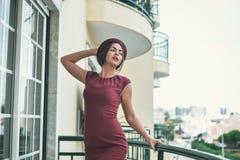 Сногсшибательная дама в темноте - красное платье представляя стоять дальше Стоковое Изображение