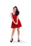 Сногсшибательная девушка в положении красного платья вскользь Стоковая Фотография