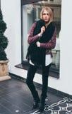 Сногсшибательная длинн-с волосами белокурая девушка представляя в модных одеждах, куртка, черные джинсы на входе к ресторану стоковое фото