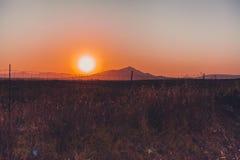 Сногсшибательный заход солнца в поле с silouhette гор Стоковые Изображения RF