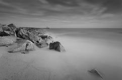 Сногсшибательный пляж с маяком в предпосылке Стоковое Изображение