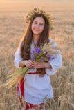 Сноп standingwith девушки на пшеничном поле на заходе солнца Стоковое Изображение