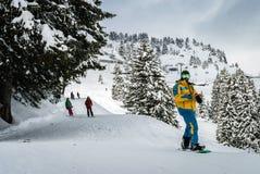 Сноубординг 2 людей катаясь на лыжах и один персоны Стоковое Изображение